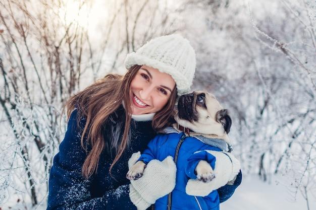 パグ犬が屋外で歩きます。冬の公園でペットを抱き締める女性。雪で覆われた冬のコートを着ている子犬。