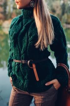 Осенняя мода. молодая женщина носить стильный наряд и держа сумку на открытом воздухе