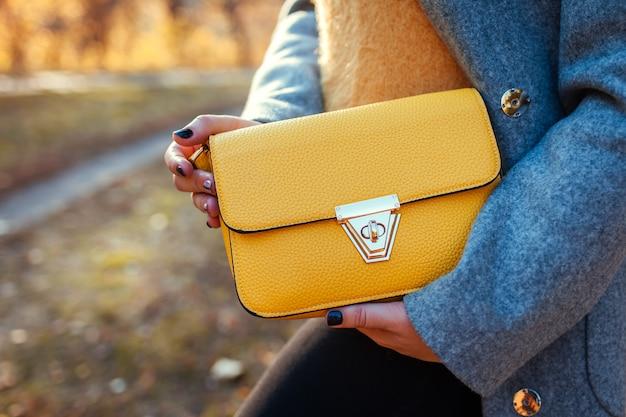 ハンドバッグ。スタイリッシュな財布を押しながらコートを着た若い女性