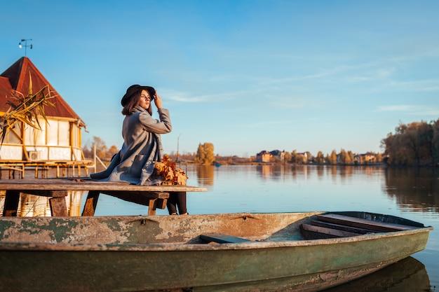秋の風景を眺めながらボートで湖の桟橋に座っている女性