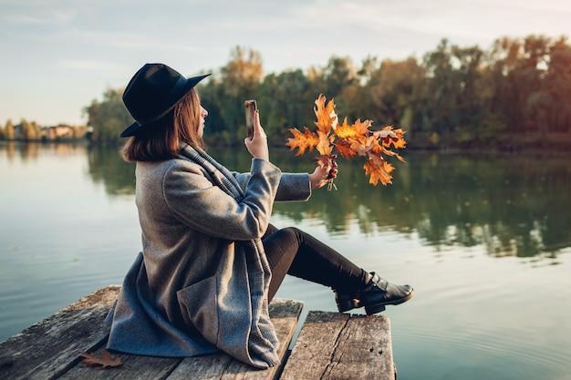 秋のシーズン。川の桟橋でスマートフォンを使用して葉と枝の写真を撮る女性