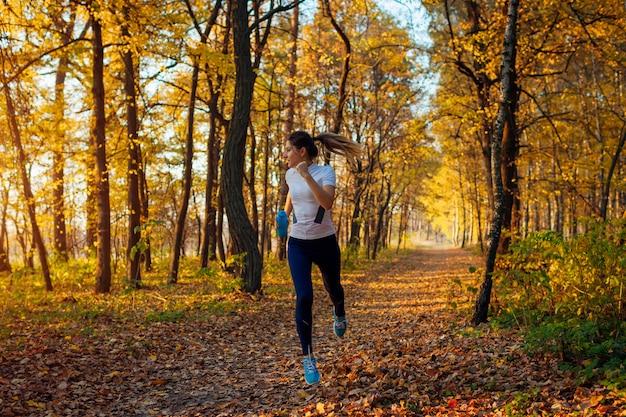 秋の公園、日没、アクティブなライフスタイルで水のボトルで走っている女性で運動するランナー