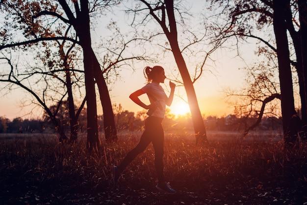 秋の公園、日没、アクティブなライフスタイルで水のボトルで走っている女性のトレーニングランナー