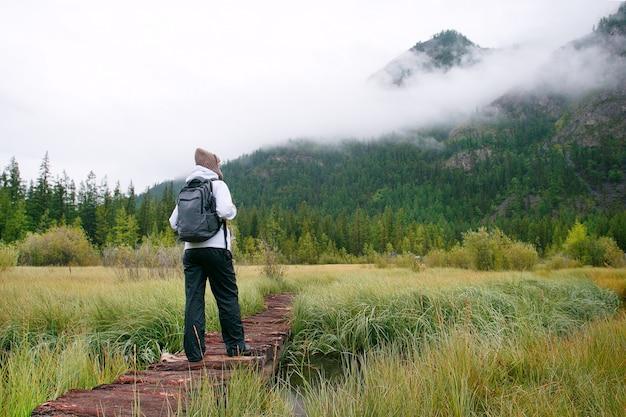 ハイキング。山の森の橋の上を歩く女性ハイカー