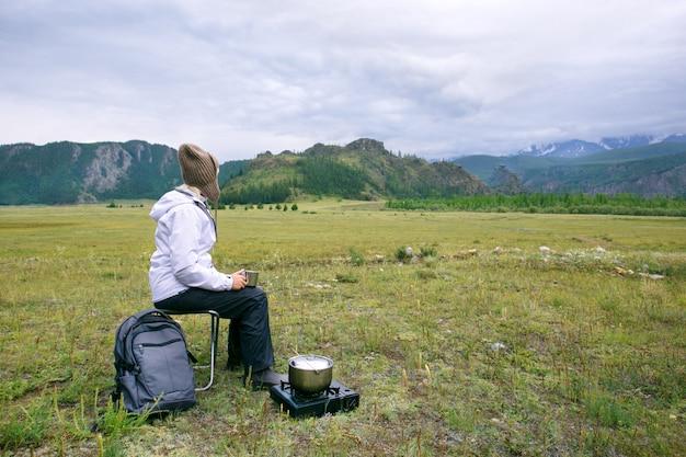 女性旅行者は、山の景色を眺めながらコーヒーまたは紅茶を飲む