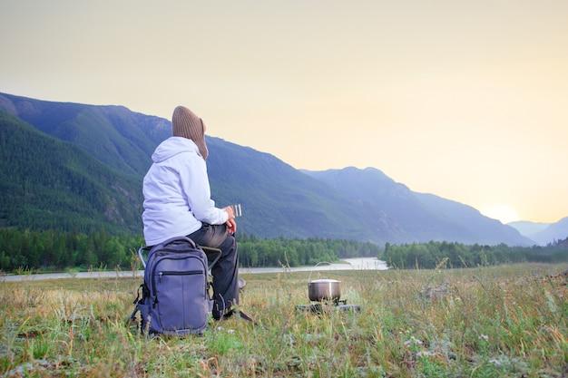 座って、マグカップで熱いお茶を楽しんでいる女性旅行者。