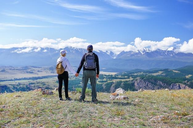 Пара туристов, взявшись за руки, наслаждаясь горы. туристы с рюкзаками, отдыхая на вершине горы и наслаждаясь видом.