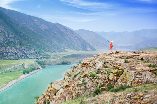 旅行ライフスタイルアドベンチャーバケーションアウトドア山。山のバックパックでサンゴの服でハイキングの女性。自由