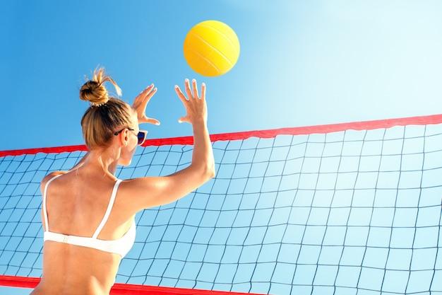 Пляжный волейболист, играет летом. красивая женщина с мячом.