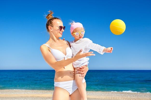 Счастливая мать и девочка, играя с пляжный мяч