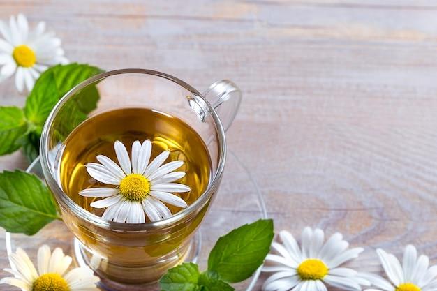木製の背景にカモミールの花とお茶のカップ