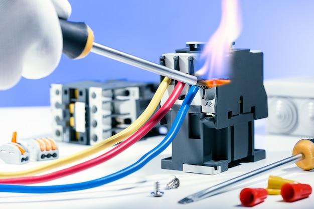電気系統の電気的ショートと火災。電気修理技術の違反