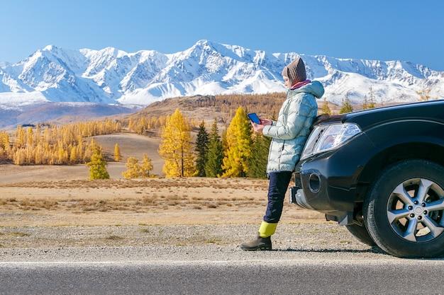 山が付いている車に座っているタブレットで女性旅行者。ロードトリップでのブログ。女性は、ソーシャルメディアのタブレットで書きます。
