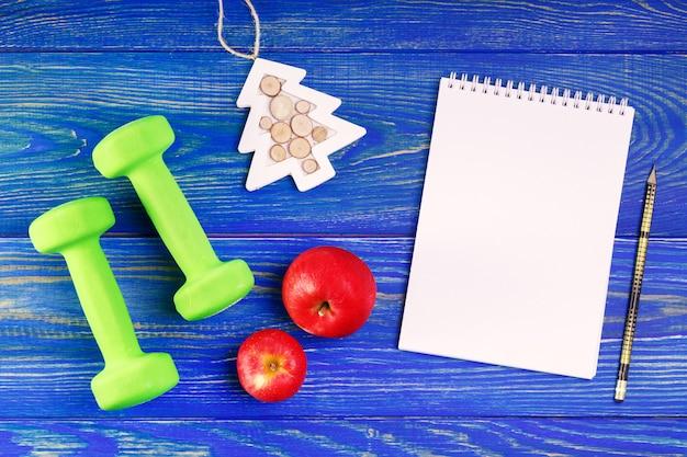 果物と木製の机の上のノートとダンベル。新年の健全な決議。