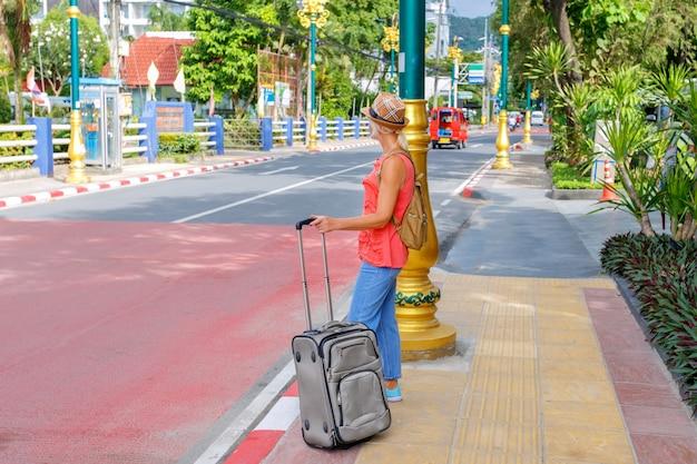 休暇旅行中に荷物を持ってバス停の近くに立っている女性観光客。アジアの国を旅行します。