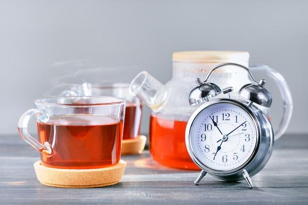 Время для чая, будильник и чайные чашки, чайник с горячим чаем на столе.