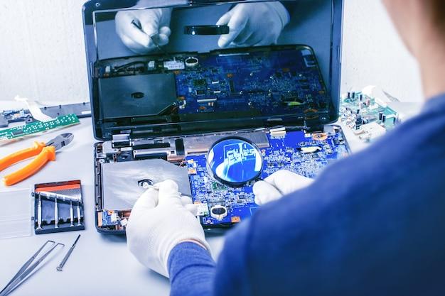 コンピューター修理。テックはマザーボードをサービスセンターに修理します。
