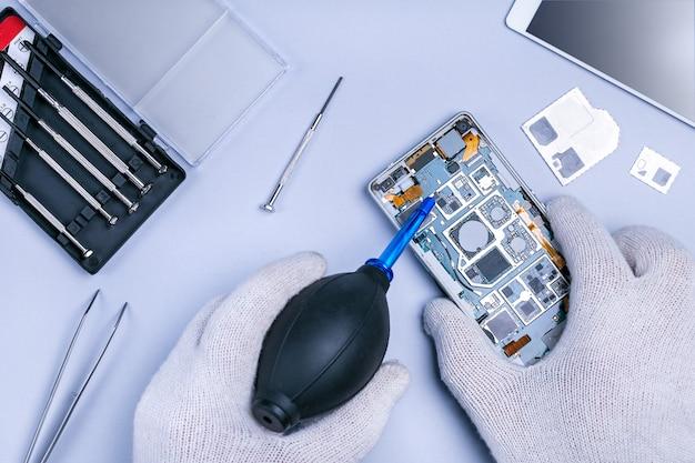 技術者の手がスマートフォンを押しながら掃除します。ガジェットのコンセプトを修復します。
