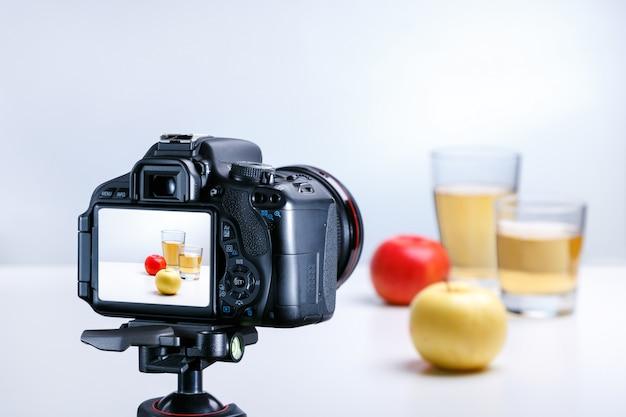 プロのカメラでジュースとリンゴの写真を撮るプロセス。閉じる