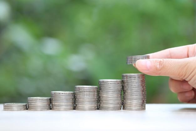 自然の緑の背景にコインのお金とグラフのスタックで成長している植物を持つ女性の手