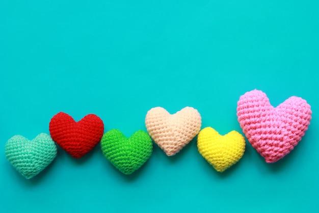 カラフルなバレンタインデーのための青い背景に手作りかぎ針編みの心