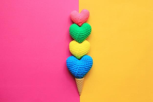 カラフルなバレンタインデーの黄色とピンクの背景にワッフルカップの手作りかぎ針編みの心