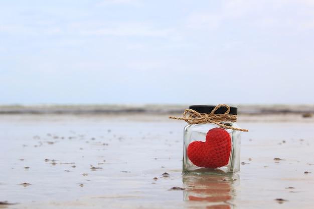 Вязаное сердце ручной работы в стеклянной банке на тропическом пляже с красивым голубым небом