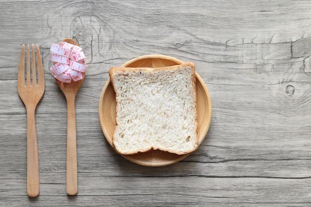 木製の背景にスプーンとフォークとメジャーテープで木製のボウルにパン
