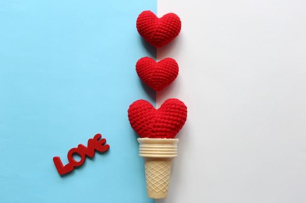 Красное вязаное сердце ручной работы в вафельном стаканчике на желто-розовом фоне на день святого валентина