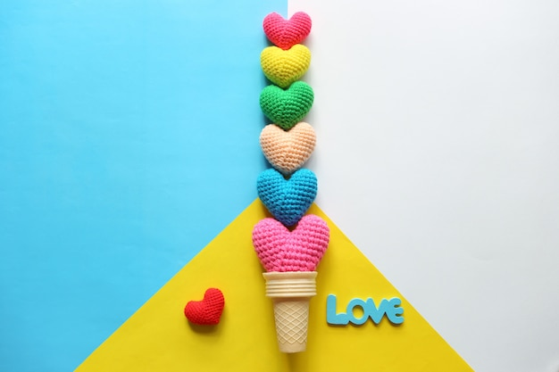 バレンタインの日にカラフルな背景にワッフルカップで手作りかぎ針編みハートのカラフルです