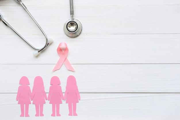 ピンクのリボンと白い木製の背景に聴診器
