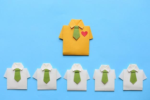 Концепция лидерства и совместной работы, желтая рубашка оригами с галстуком и ведущая среди маленькой желтой рубашки