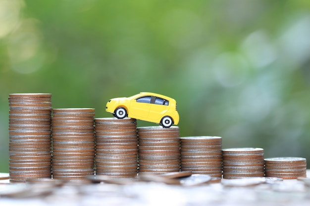 Миниатюрная желтая модель автомобиля на растущей стопке монет на природе