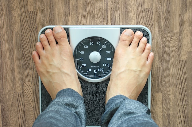 チェック体重、ダイエットの概念の体重計の男性