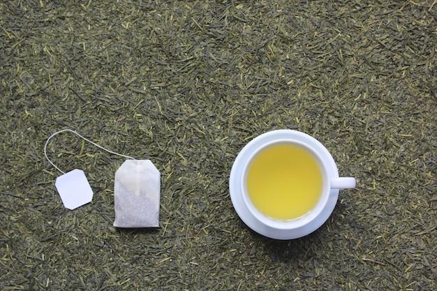 Вид сверху чайная чашка с пакетиком чая на фоне сухих чайных листьев