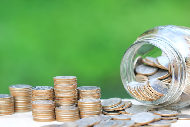硬貨お金と自然の緑のガラス瓶のスタック