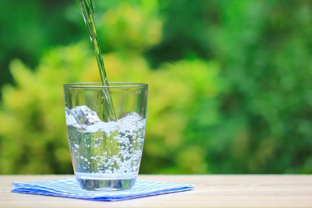 Крупным планом стакан воды на столе