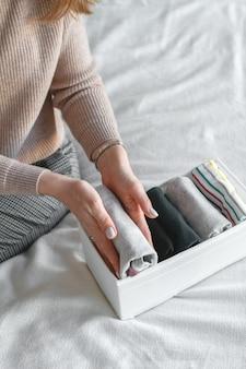 Женщина складывает футболки в ящик. женщина убирает в шкафу. вертикальное хранение одежды.