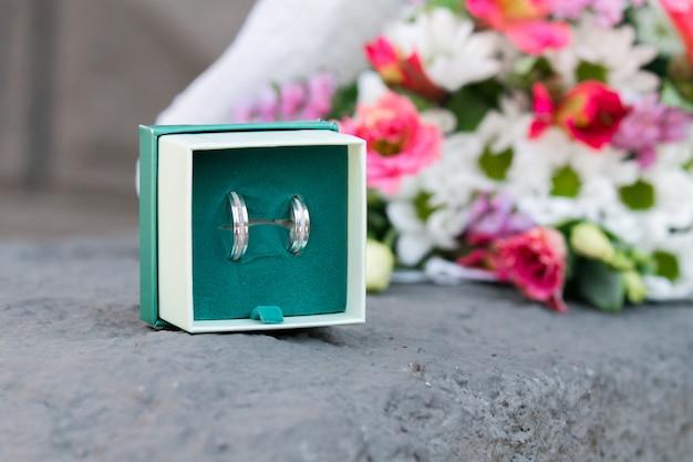 白とピンクの花の花束に近い結婚指輪