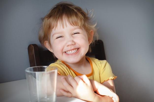 テーブルのクローズアップで灰色の背景に面白い子の肖像画。おかしな悪魔