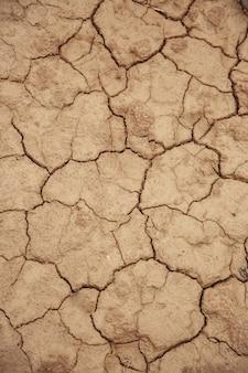 ひびの入った赤い粘土土のクローズアップ、干ばつの概念のテクスチャ