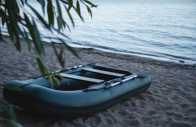 ビーチの砂の上のオールと膨脹可能なグリーンボート
