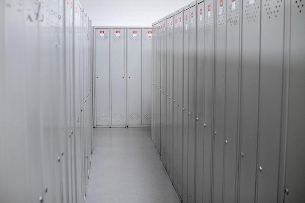 Ряд стальных серых шкафчиков вдоль белой стены.