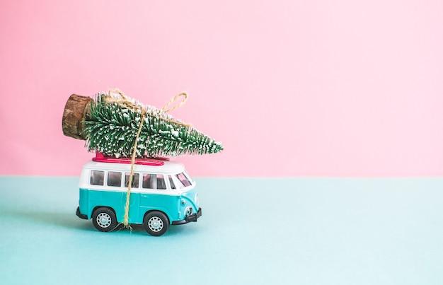 屋根の上の新年のクリスマスのモミの木とヒッピーバスミニチュア小型車バナーパーティーテーマ