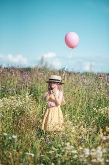 黄色のドレスと帽子、夏に花のフィールドを歩いてかわいい女の子