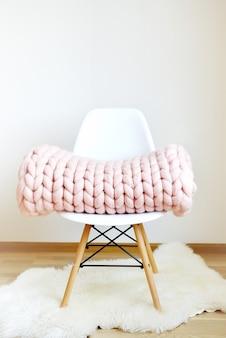 白い木製のスツール椅子ホームスカンジナビアスタイルで編まれた巨大なピンクの格子縞毛布ウール