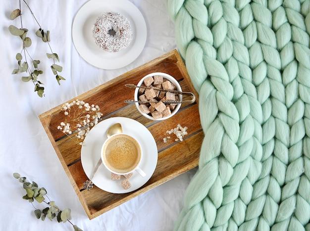 カプチーノドーナツカップと緑のパステル調の巨大な格子縞の寝室の朝