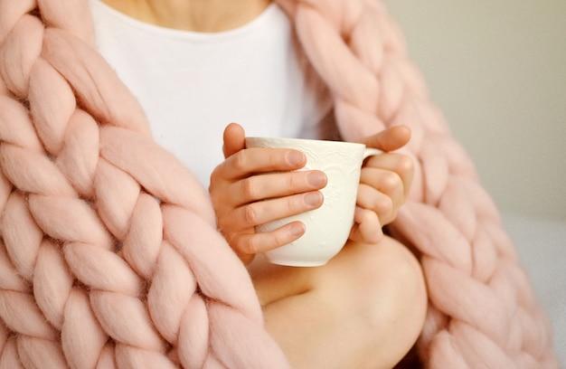 カプチーノのカップとピンクの巨大なメリノウールチェック柄の毛布が付いているベッドの上に座っている若い女性。