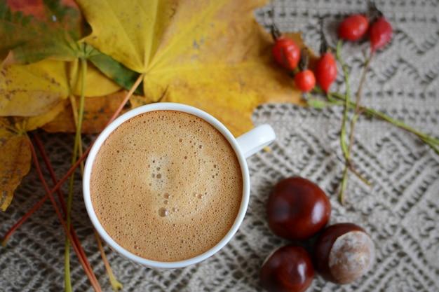Чашка кофе напиток клен желтые листья каштаны золотая осень веселый солнечный свет утренняя концепция тонированное