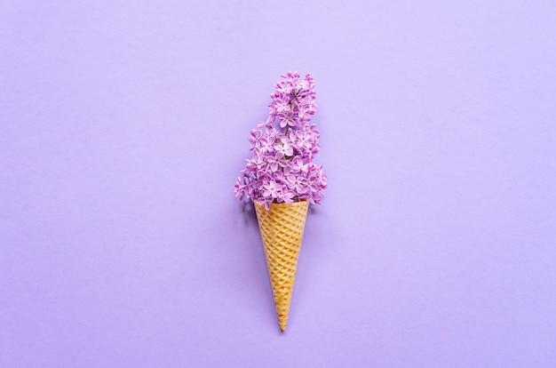 紫色のライラックの花とアイスクリームコーンの組成。平干し。上面図。創造的な夏のコンセプト